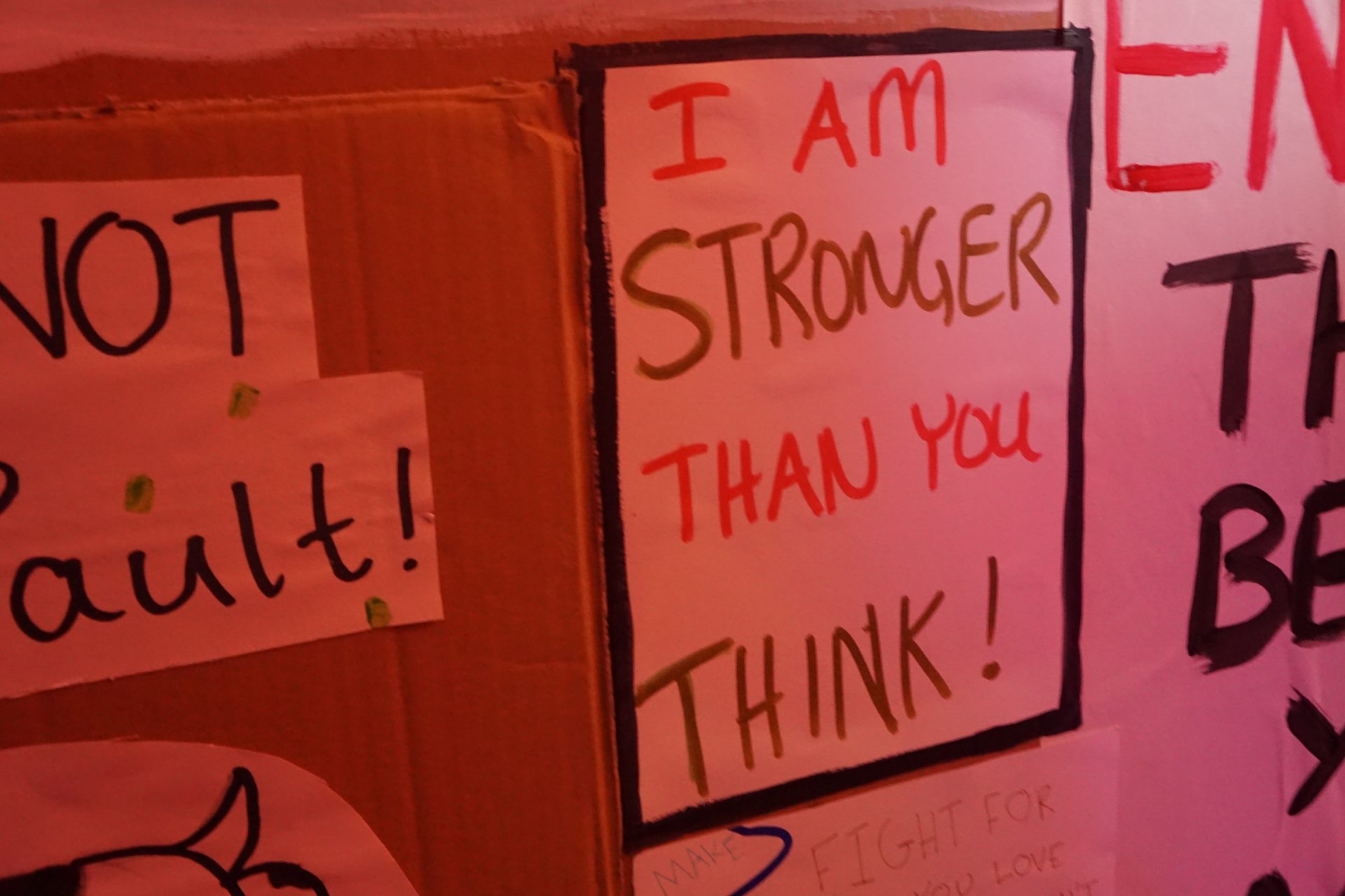 A protest banner made by Doorstep Youth Theatre, in a red light, reads 'I am stronger than you think'