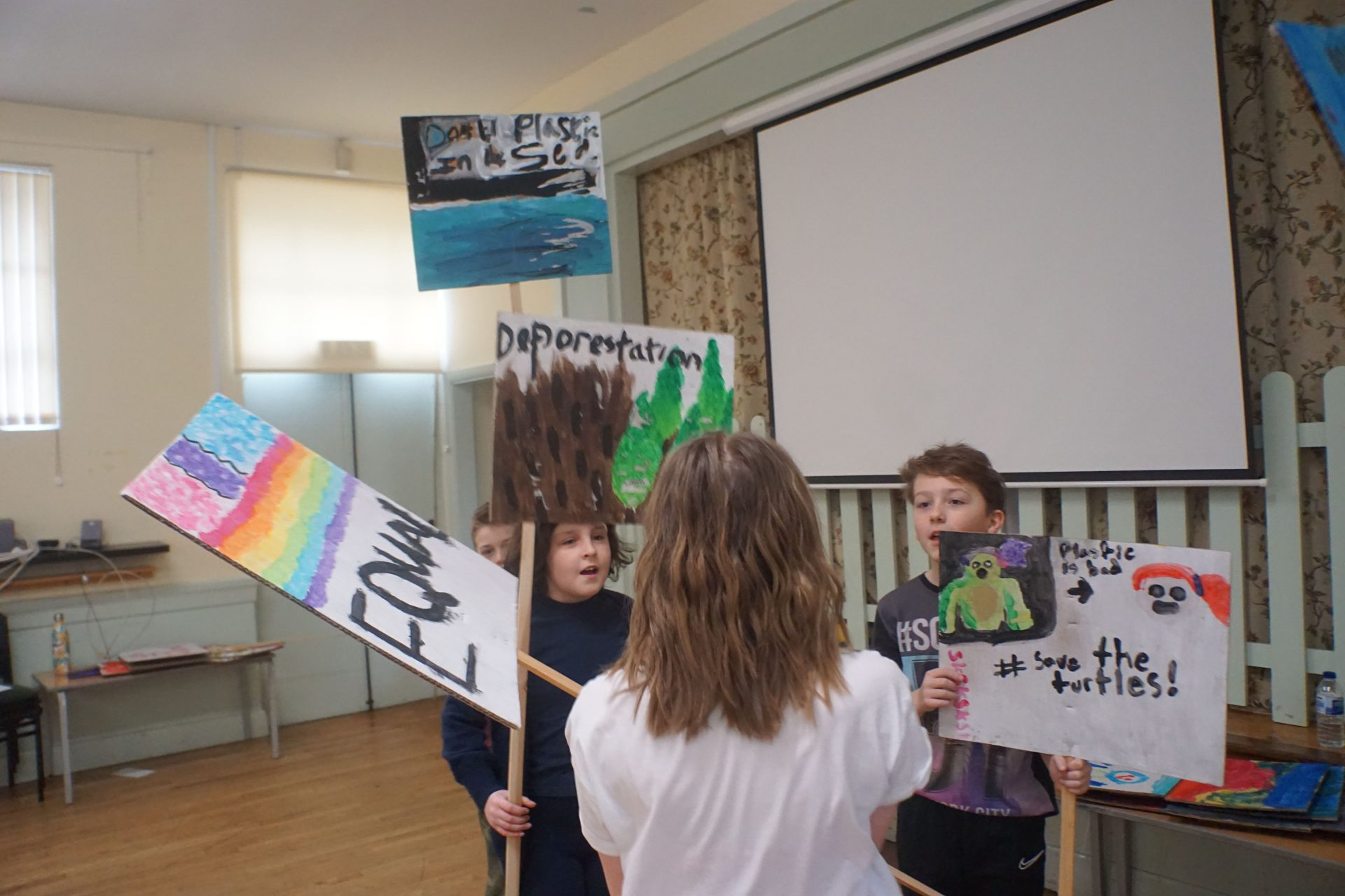 A Doorstep Arts' Saturday group designing protest banners for causes they care about. Four childrne hold colourful signs about equality, deforestation and saving the turtles.