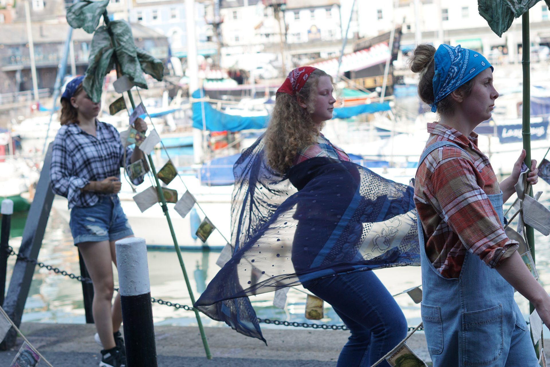 Three young people hold protest banners that look like cabbages and dress as farmers on a perfomrance protest, there are boats in the background and one femme holds a long blue scarf flowing in the wind.