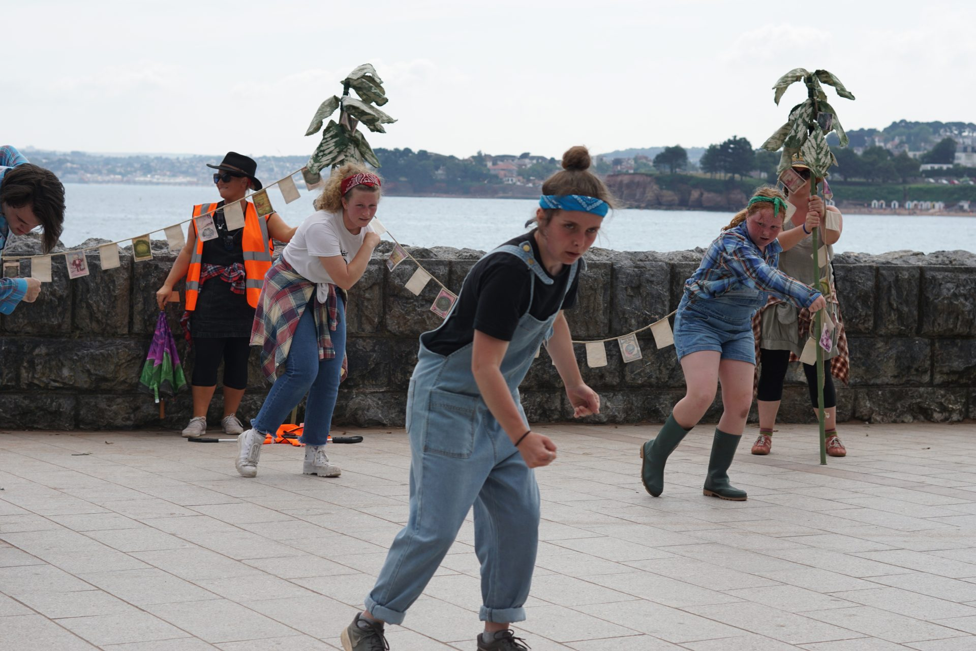 Young people at Doorstep Arts performing in a performance protest in Torbay, femmes wear dungarees and hold cabbage inspired protest banners
