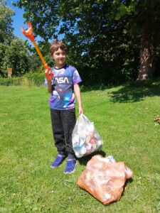 Daniel holds an orange litter grabber in one hand and a bag full of rubbish that they have collected in the other hand. Another bag of litter sits infront of Daniel as he stands happily in the park.